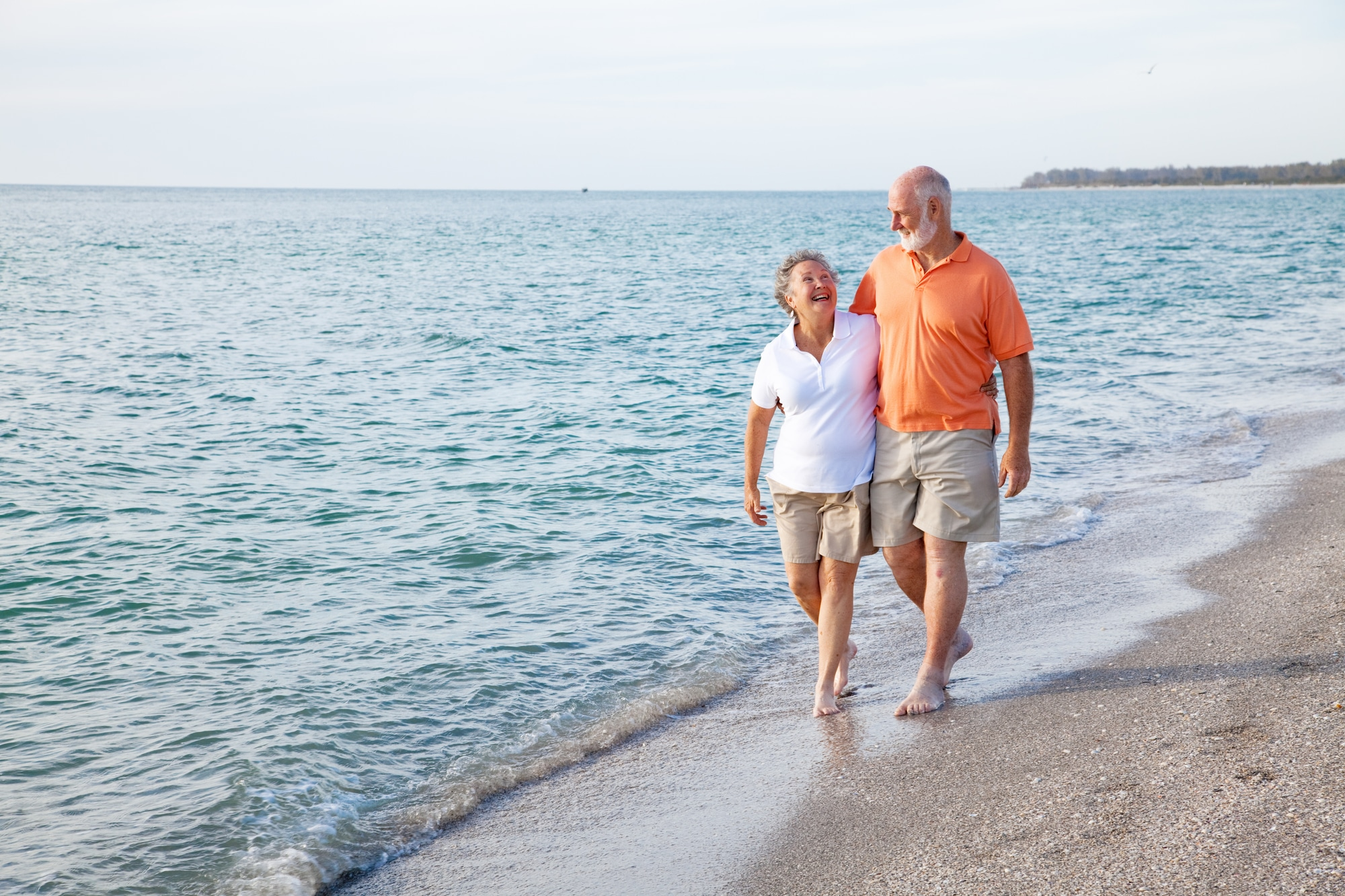elderly couple laughing and walking on a beach